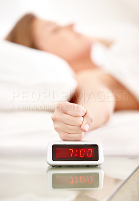 Buy stock photo A young woman slamming her fist down on her alarm clock