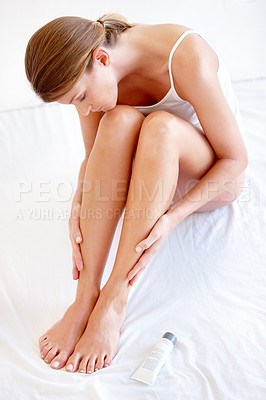 Buy stock photo A naturally gorgeous young woman applying cream to her legs on her bed