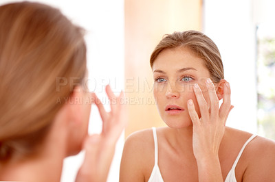 Buy stock photo A naturally gorgeous woman applying moisturizing cream in a mirror