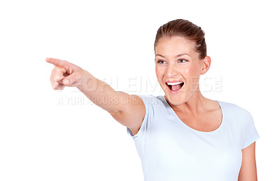 Buy stock photo An excited young woman pointing at something while isolated on a white background