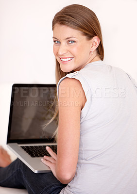 Buy stock photo Rear view of a lovely young woman working on her laptop