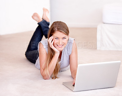 Buy stock photo A beautiful young woman using her laptop while lying on the floor