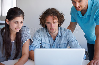 Buy stock photo Cropped shot of three coworkers gathered around a laptop in the office