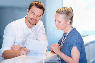 Buy stock photo Cropped shot of two coworkers looking over paperwork in the office