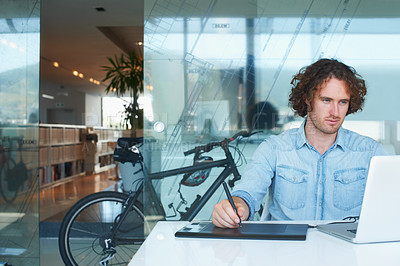 Buy stock photo Cropped shot of a young businessman working on his laptop in the office