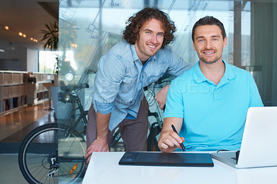 Buy stock photo Cropped shot of two coworkers working on a laptop in the office