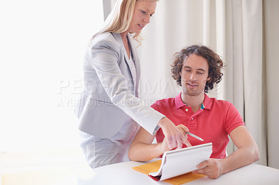 Buy stock photo Cropped shot of a young businessman getting some advice from his supervisor