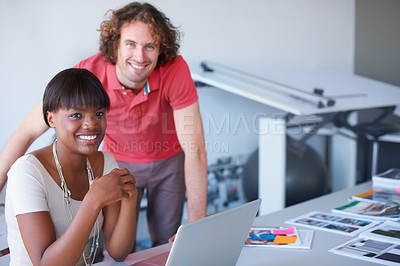 Buy stock photo Cropped shot of two young businesspeople working on a laptop