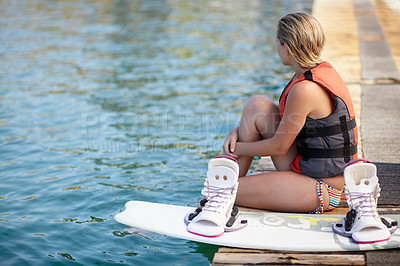 Buy stock photo A young girl looking away while sitting on a pier next to a wakeboard