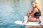 Portrait of a pretty young girl sitting on a jetty next to a wakeboard