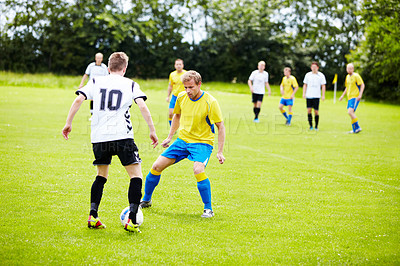 Buy stock photo A group of soccer players in the middle of a game