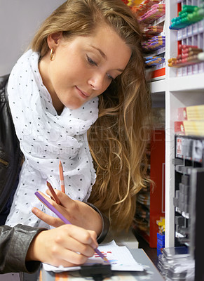 Buy stock photo Shot of a young female artist trying out different writing equipment in an art store