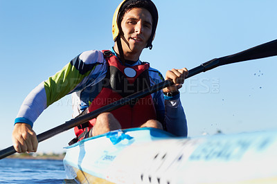 Buy stock photo Shot of a young man kayaking in a river