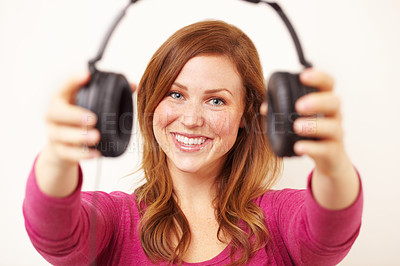 Buy stock photo Portrait of an attractive young woman offering you a pair of headphones