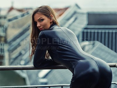 Buy stock photo Cropped view of a sultry young woman in a skin-tight suit leaning over a railing