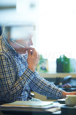 Buy stock photo A senior businessman wearing a headset while sitting in his office