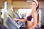 A fit young woman using the treadmill at gym