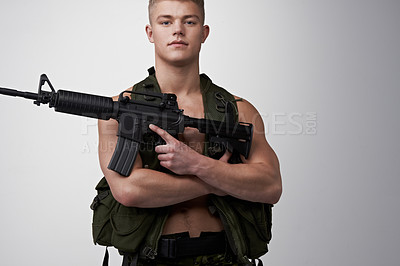 Buy stock photo Young soldier holding an automatic rifle and looking at the camera