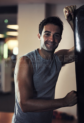 Buy stock photo A smiling handsome man wearing sport clothing and leaning against a punching bag at the gym
