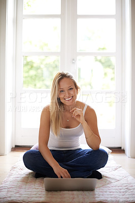 Buy stock photo Smiling young woman sitting on the floor and using her laptop