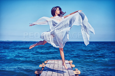 Buy stock photo A beautiful young woman dancing on the pier