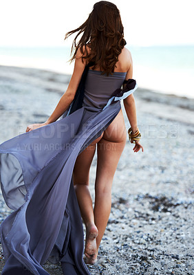 Buy stock photo Rear view of a young woman walking on the beach with her bum exposed