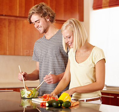 Buy stock photo A young couple making dinner in the kitchen