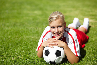 Buy stock photo Portrait of an attractive female football player lying chest down on the grass and leaning on a soccer ball