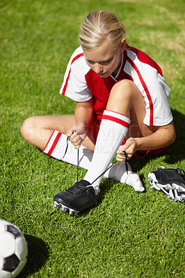 Buy stock photo Shot of a female soccer player tying up her shoes while lying on the grass