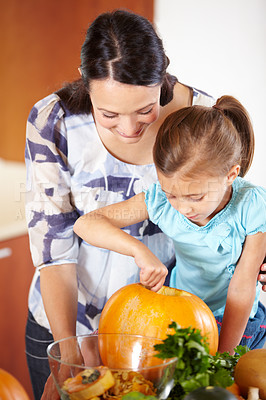 Buy stock photo A happy young mother helping her daughter to carve a pumpkin in the kitchen