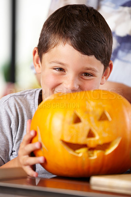 Buy stock photo A happy young boy showing off his Jack O'lantern to the camera