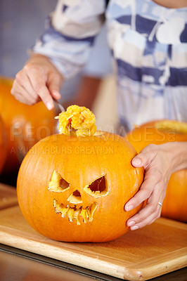 Buy stock photo Closeup of a woman hollowing-out a Jack O'lantern for Halloween