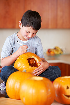 Buy stock photo A little boy sitting cross-legged and drawing a face on a Jack O'lantern