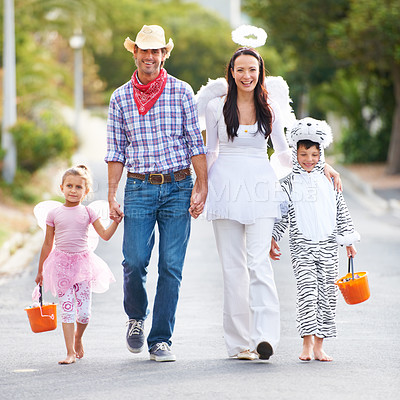 Buy stock photo Full length shot of a family walking down the road in their Halloween costumes
