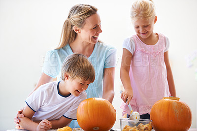 Buy stock photo A mother, her son and her daughter hollowing out pumpkins for halloween