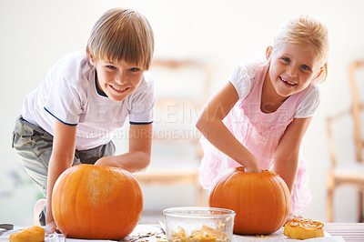 Buy stock photo Portrait of a little boy and girl hollowing out their jack-o-lantern