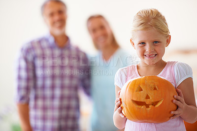 Buy stock photo Portrait of a little girl holding her jack-o-lantern with her parents blurred behind her