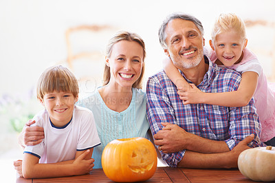 Buy stock photo Portrait of a family of four sitting with their jack-o-lantern at home