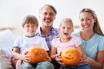 Buy stock photo Portrait of a family of four showing you their carved pumpkins