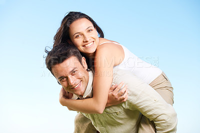 Buy stock photo A handsome young man  giving his girlfriend a piggyback outdoors