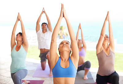 Buy stock photo Young yoga instructor leading a class in meditation