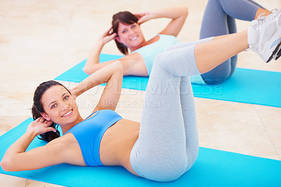 Buy stock photo Young women doing a sit up during a pilates class