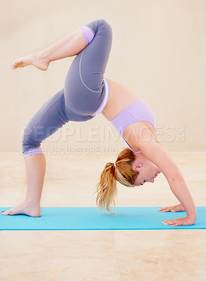 Buy stock photo Lithe woman in a yoga position while doing yoga by herself
