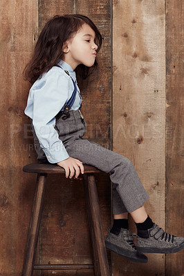 Buy stock photo Shot of a cute little boy in old-fashioned overalls sitting on a stool