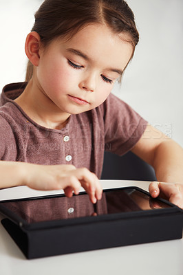 Buy stock photo Shot of an adorable little girl using a digital tablet