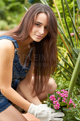Buy stock photo Portrait of an attractive young woman planting some new flowers in her garden