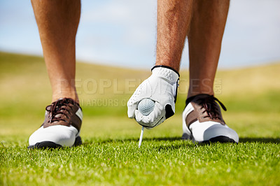 Buy stock photo A golfer putting his tee into the ground on the golf course