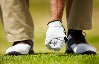 Buy stock photo Cropped image of a golfer putting his golfball on the tee