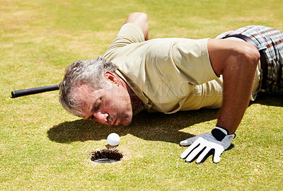 Buy stock photo A mature golfer on his stomach about to blow his golf ball into the hole
