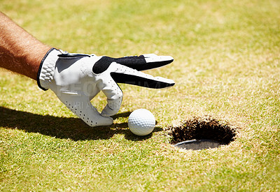 Buy stock photo A golfer about to flick a ball into the hole